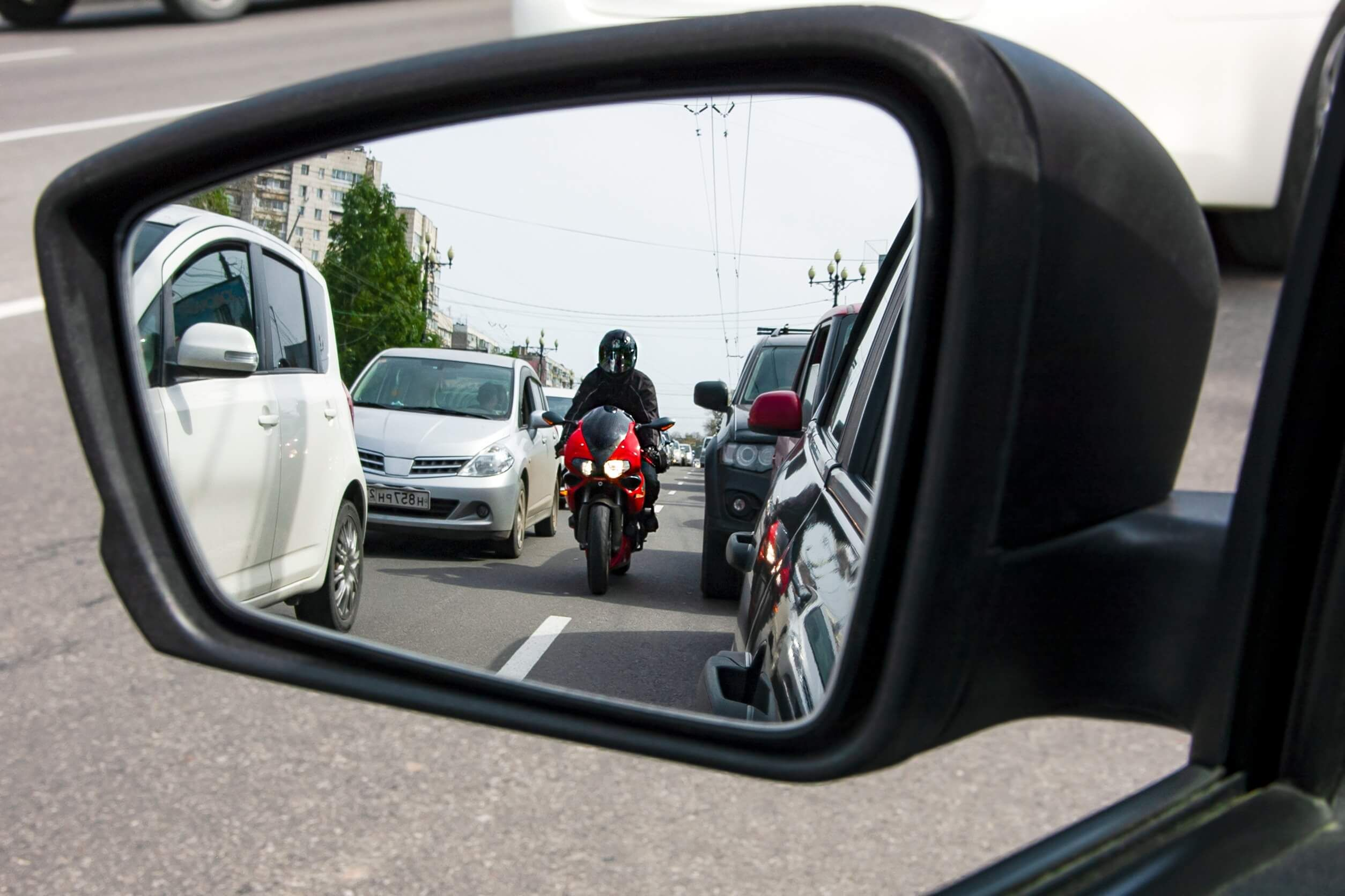 A motorcycle lane splitting and about to cause an accident.