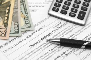 Chapter 11 bankruptcy document with money and calculator.