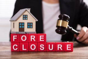 Foreclosure concept with toy house and lawyer with gavel.