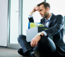 Sad middle-aged businessman sitting with his personal belongings after filing for bankruptcy