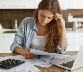 Woman getting worrried on the expenses she have incurred.