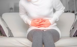 Woman holding her stomach to represent pain due to a bile duct injury