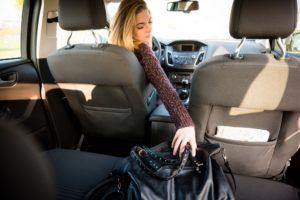 Young woman reaching purse from back seat.