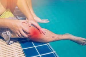 Swimmer suffering from a knee injury after a slip and fall accident