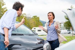 Woman driver and angry man arguing about the damage of the car.