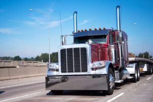 Classic big rig semi truck in dark red and flat bed semi trailer going to warehouse for loading cargo