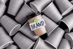 one coffee cup in color with a brand label on it over a pile of plain ones