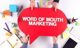Two people holding red sign with word of mouth marketing