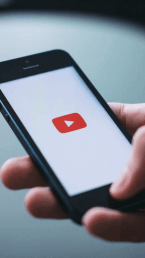 person holding a phone using youtube