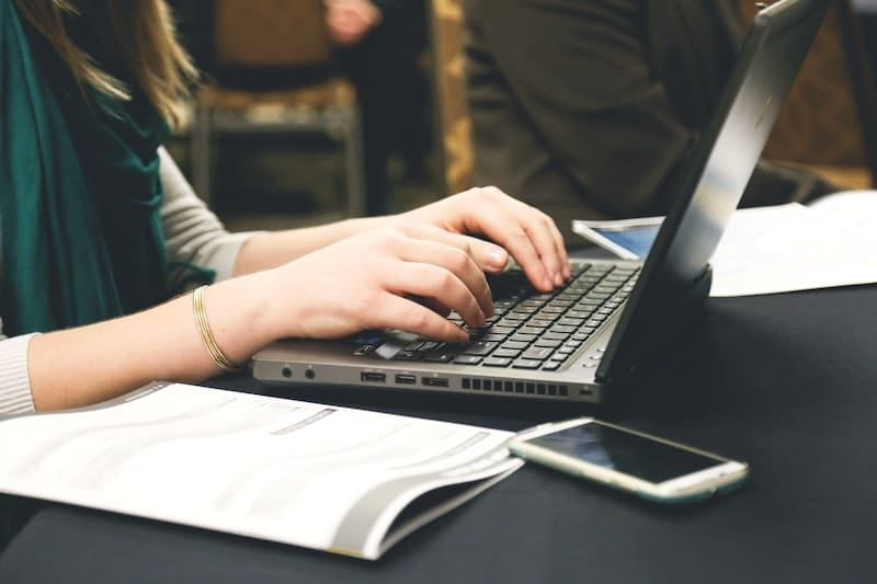 a woman at a table typing on her laptop