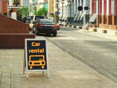 Sidewalk car rental sign