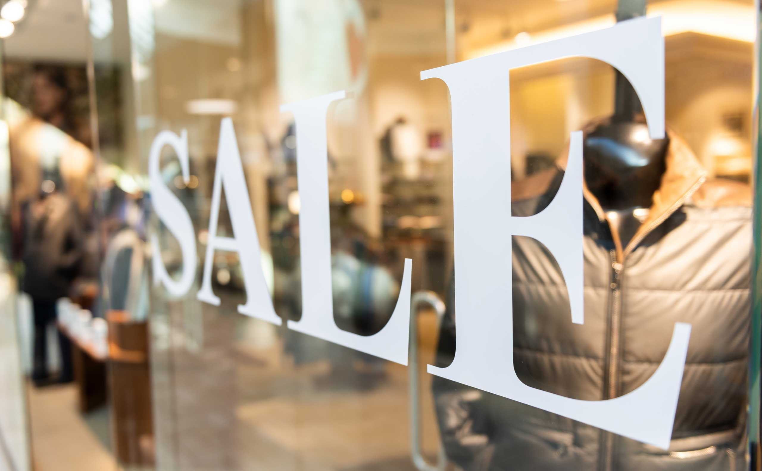 Window decal stating sale in white letters