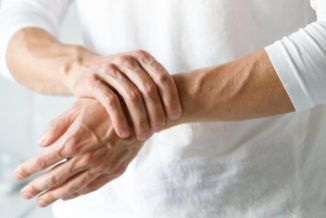 man holding his hands suffering from crps