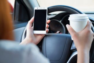 A Woman drinking coffee and texting while driving