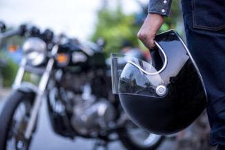A motorcycle driver holding a helmet