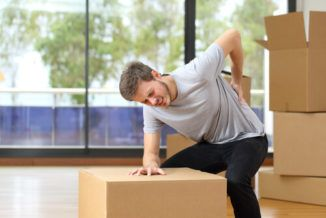 a man leaning his right hand on a box with his left hand pressing his aching lower back-workplace injuries