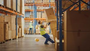 a man in a warehouse, in an out balance position where a stock of boxes might fell on him - dangerous warehouse work -