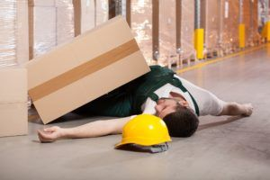 a warehouse worker fell on the floor after he was hit by a heavy box - warehouse hazards