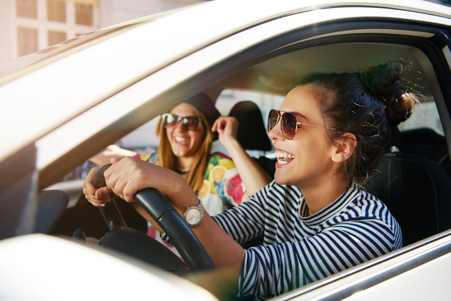 teen driver with a passenger laughing