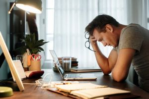 man stressed trying to decide on a personal injury lawyer
