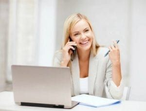 Female employee talking over the phone and holding the pen on the other hand