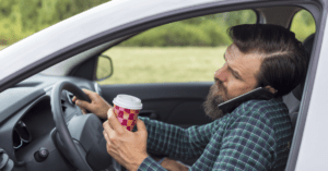 A man speaking on phone and drinking coffee while driving his car