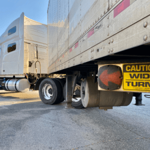 """sign read"""" Caution ,Wide turns""""with orange led arrow underneath the truck"""
