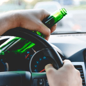 drunk young man driving car with bottle