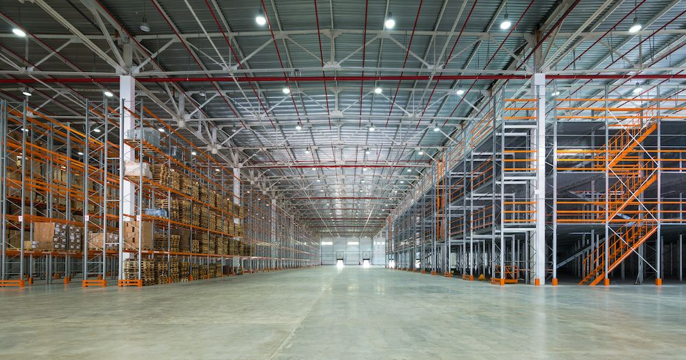 A sprawling warehouse, mostly empty but with lots of shelves.