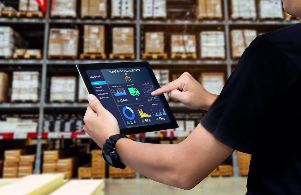 A worker holds up a tablet in a rental warehouse space.