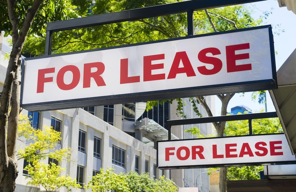 A For Lease sign hangs outside a commercial lease building.