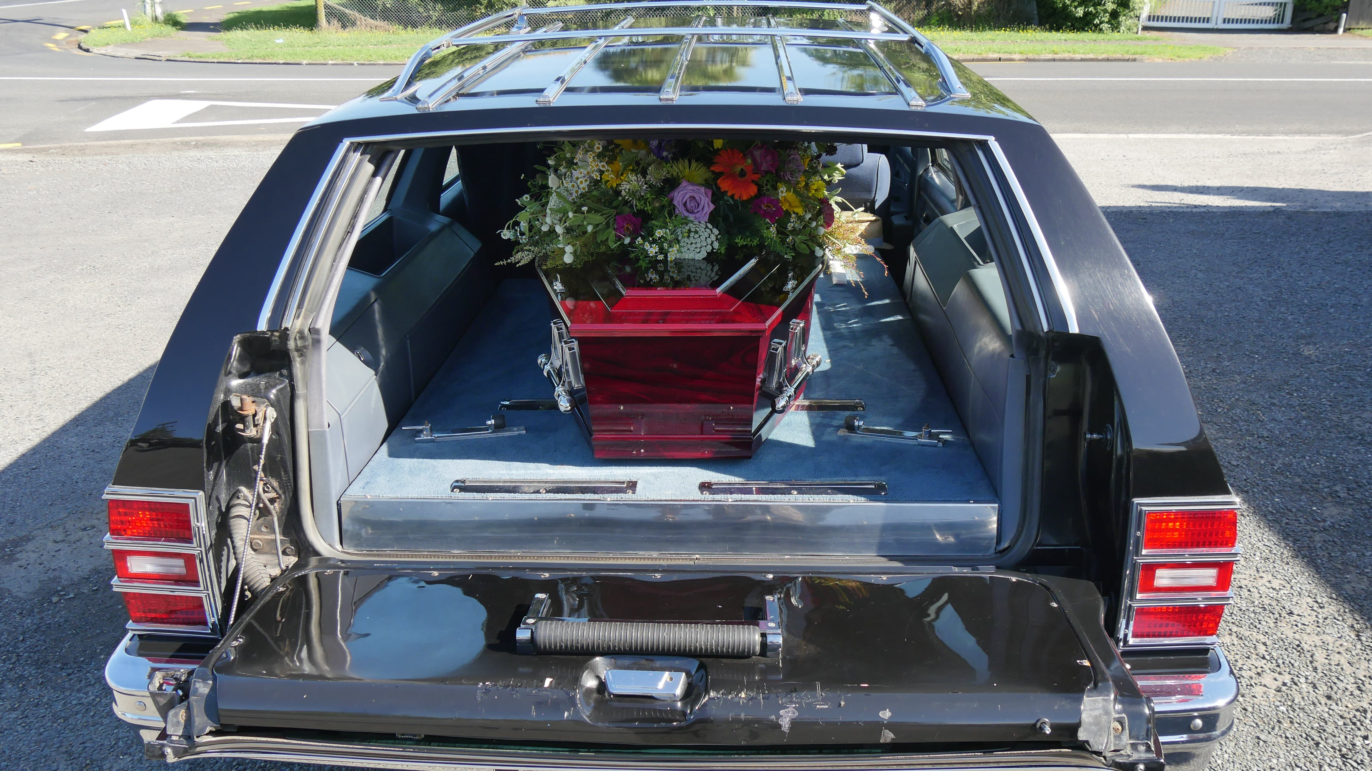 Funeral hearse with colorful flowers above casket.