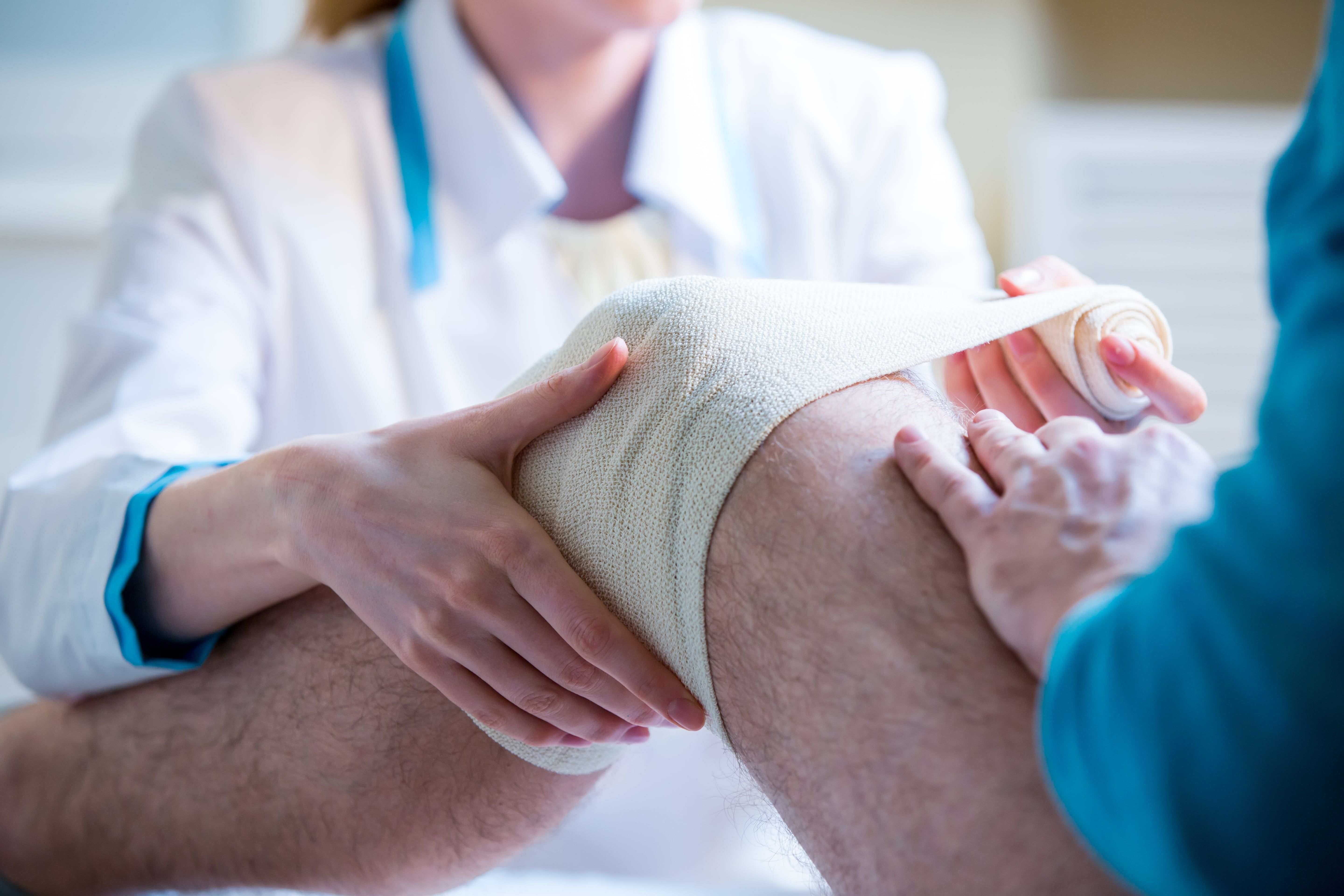 Doctor putting bandage on the patient's knee injury.