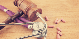 gavel, stethoscope and pills on wooden background