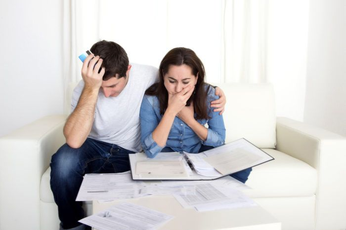 Frustrated couple sitting in front of their bills
