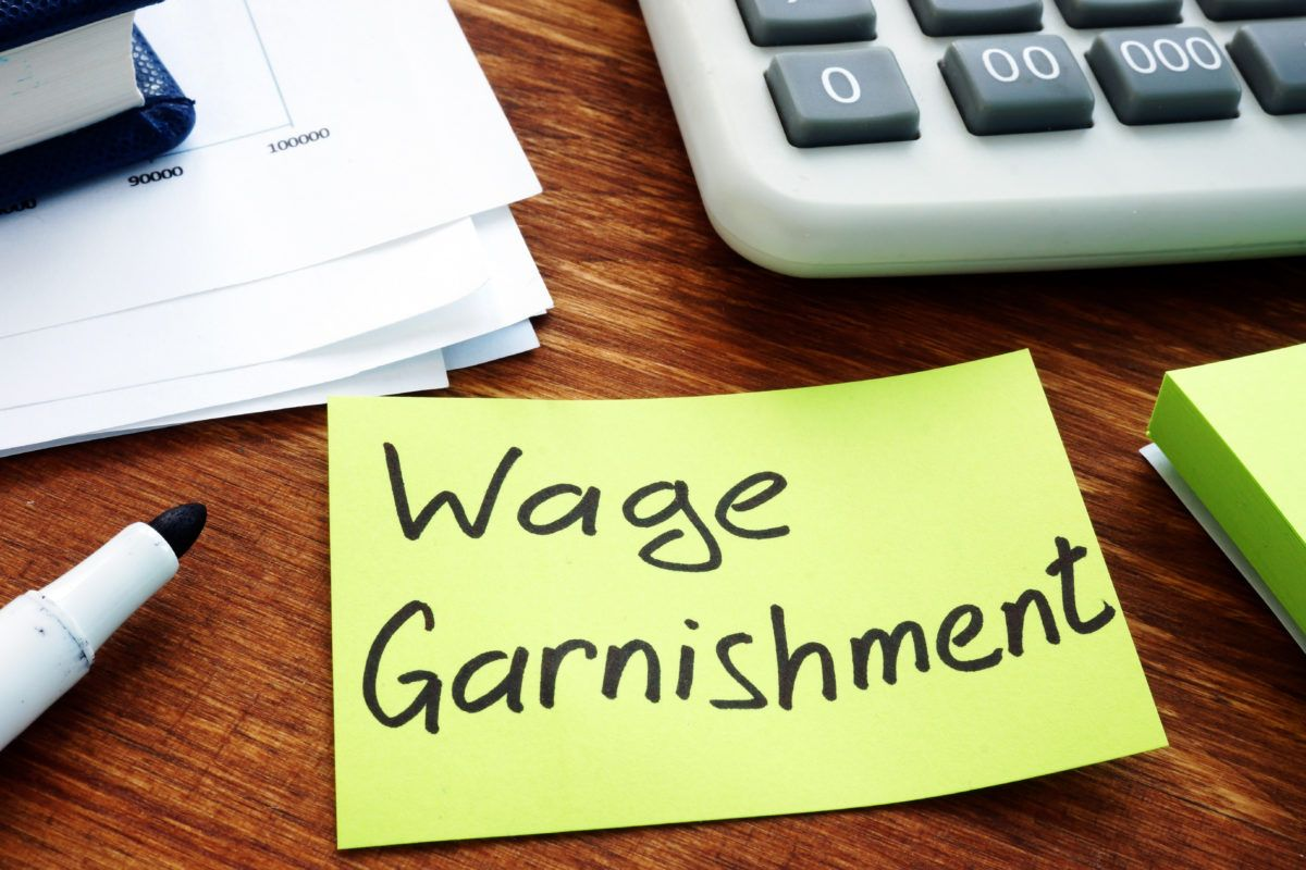 """wage garnishment"" written on a sticky note near credit card bills"