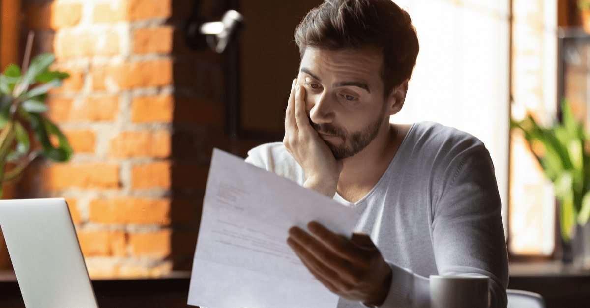 confused frustrated young man looking at debts