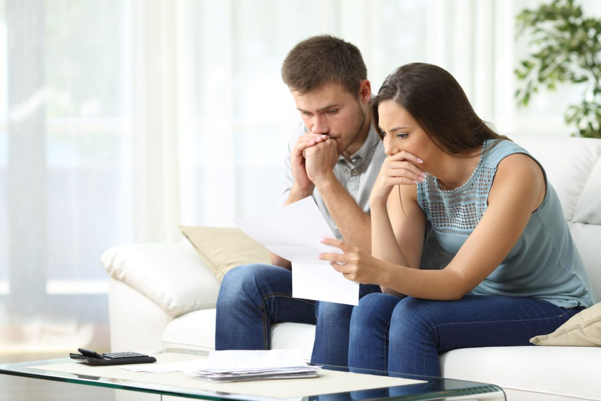 worried couple reading foreclosure notice