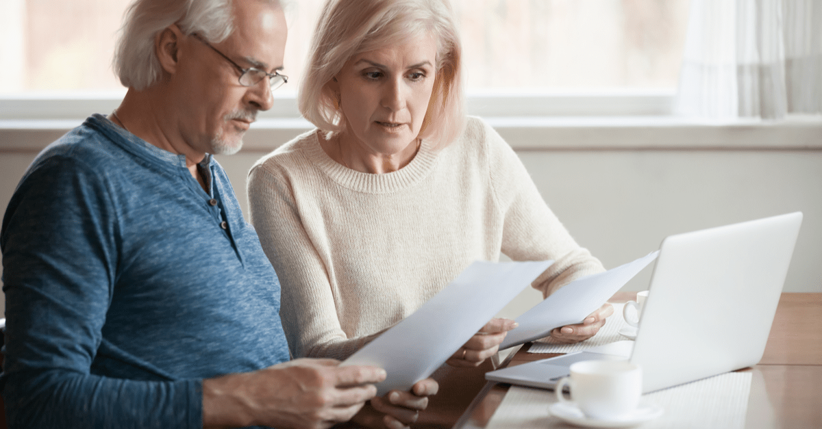 serious worried senior couple calculating bills