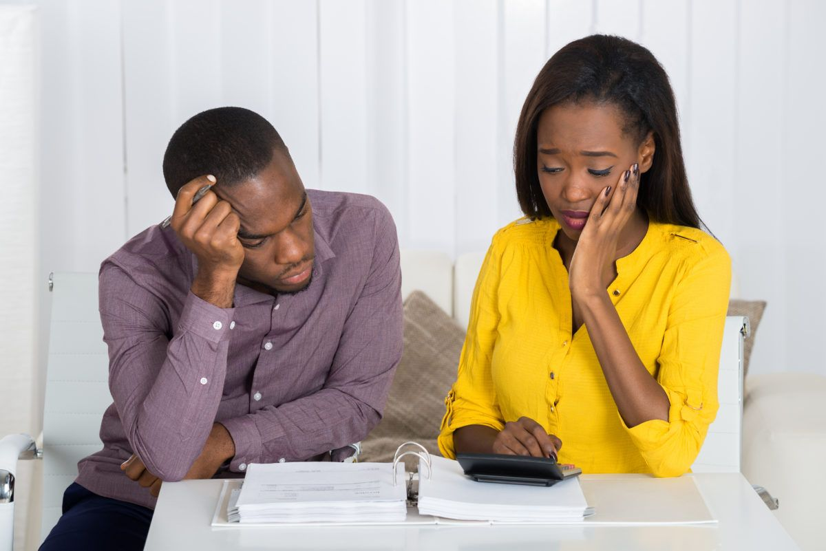 a couple reviewing their bank statements after a debt collector garnishes their wages