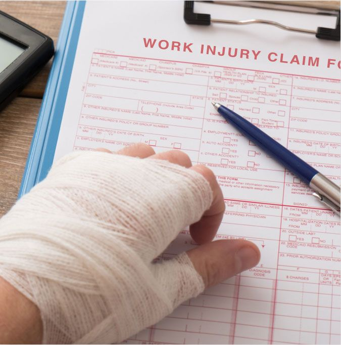 A worker filling out a work injury claim form.