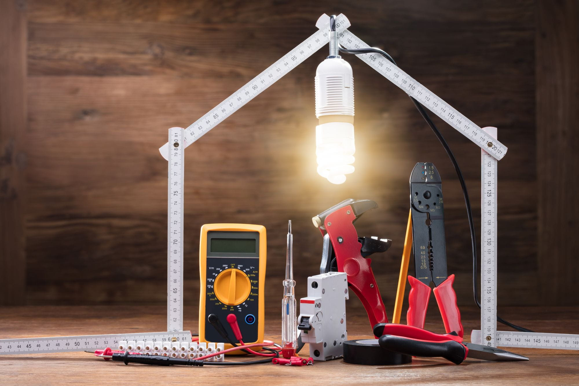 Repair Tools Under The Illuminated House Made With Measuring Tape On The Wooden Table Answering Electrical Questions
