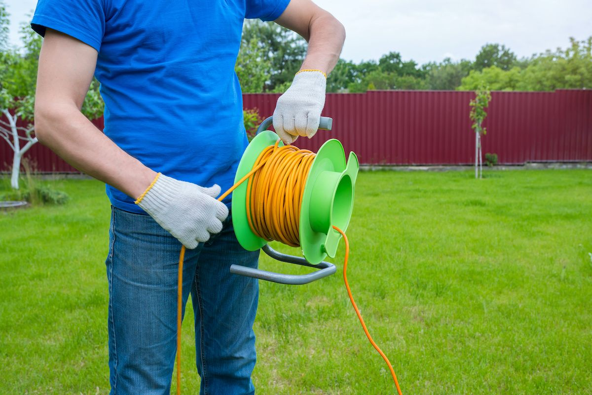 An electrician unrolls an orange cord in a bright green backyard.