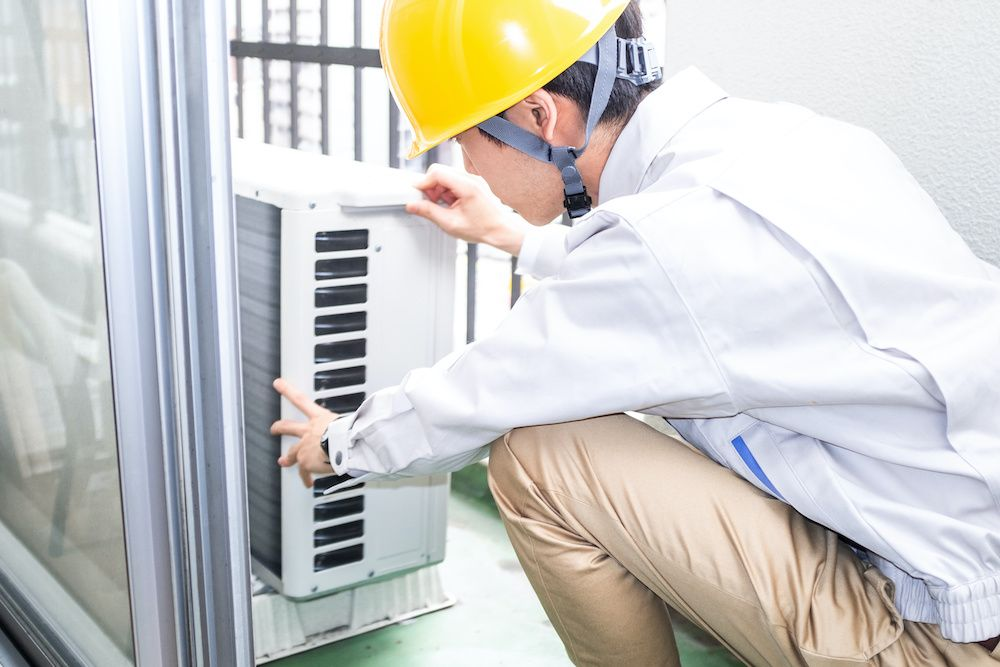 A worker in a yellow helmet performs an AC replacement.