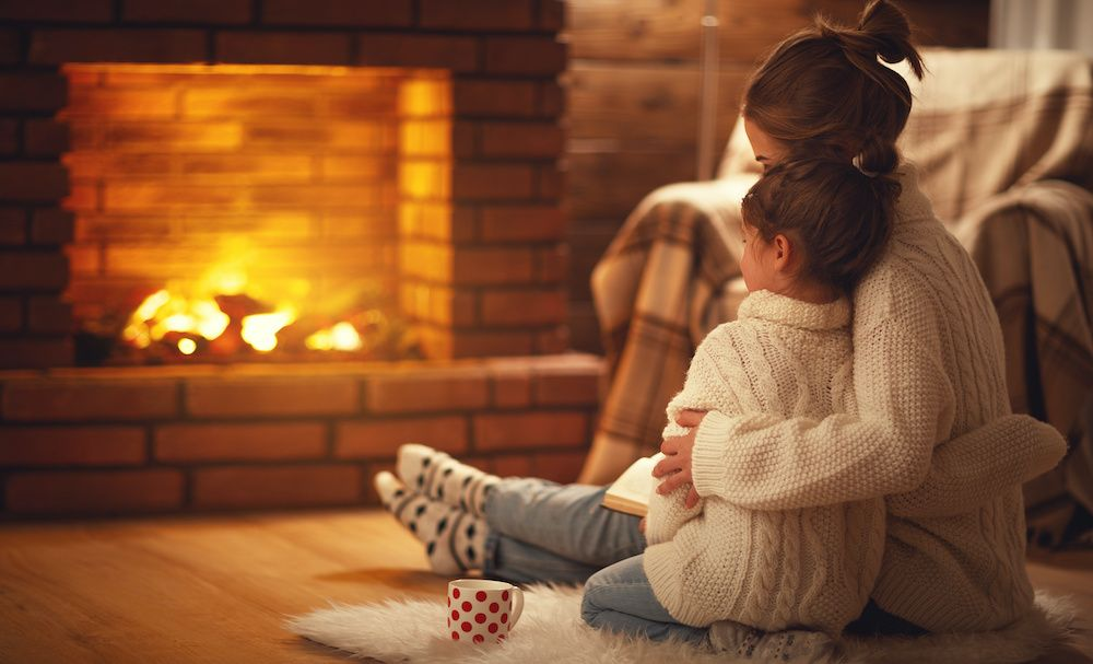 A mother and daughter relax in front of the fire.