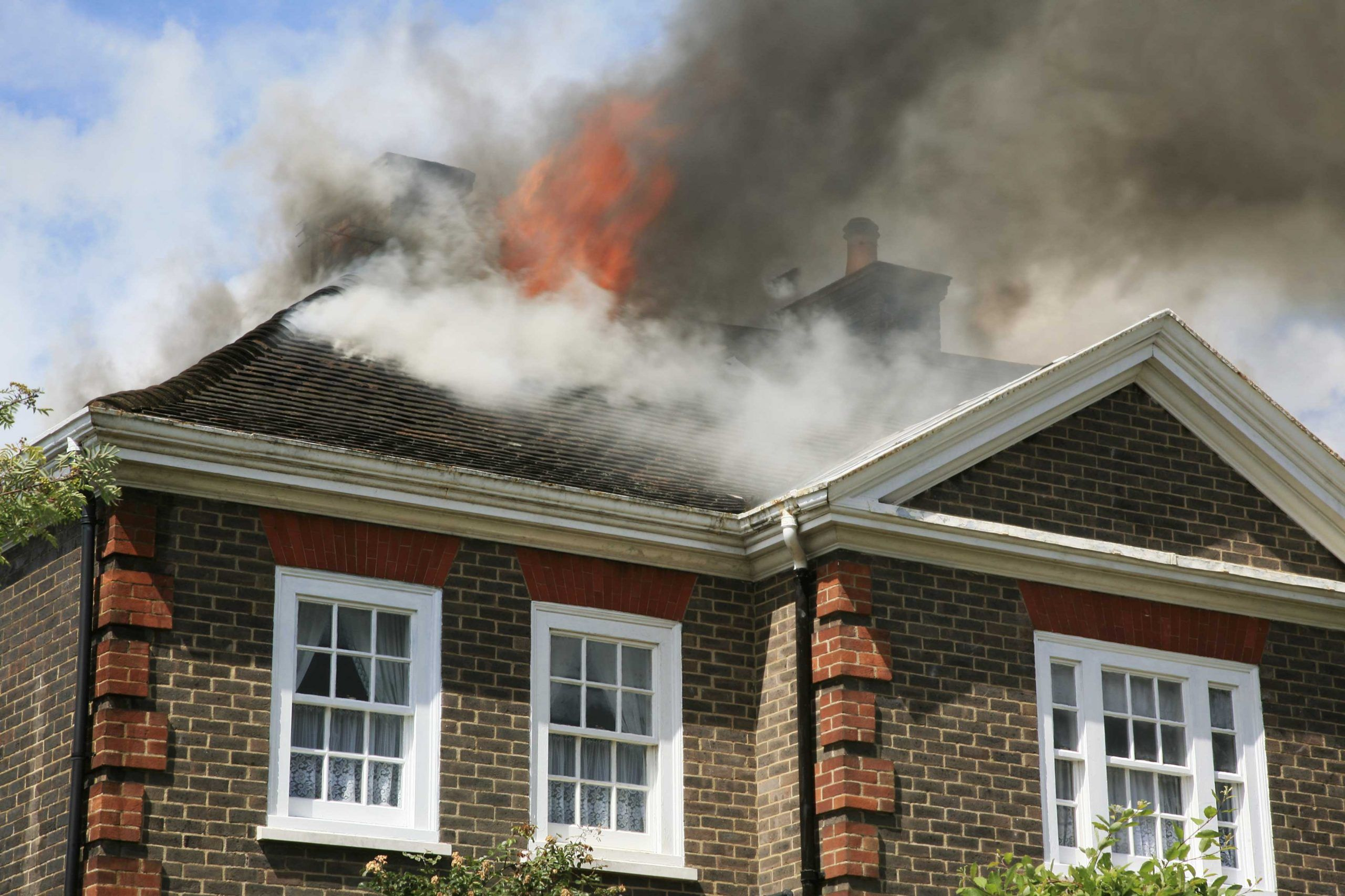 House on fire with fire and smoke damage