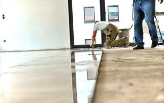 A man cleans water off a half-finished floor.