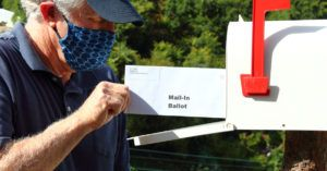 Man mailing in a ballot during the covid-19 pandemic.