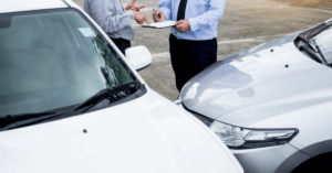 insurance agent writing on clipboard after a car accident
