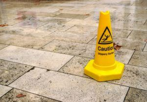 yellow cone with caution slippery surface sign, on wet pavement tiles.